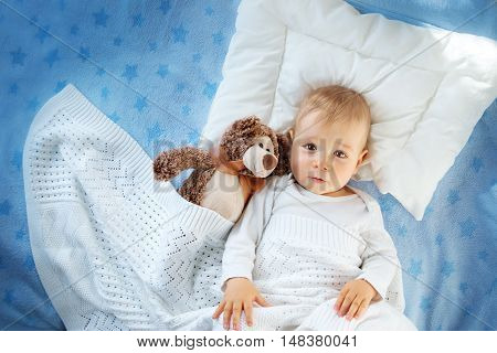 One year old baby lying in bed with a plush teddy bear. Child sleeping on soft blue blanket with stars