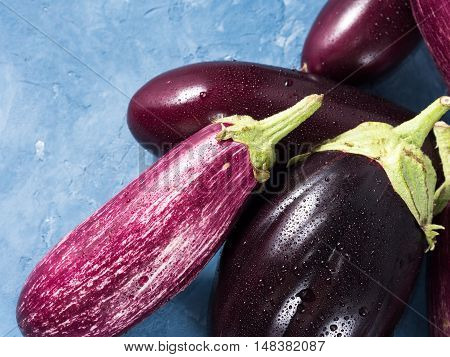 Different colored eggplants on blue textured background. Top view