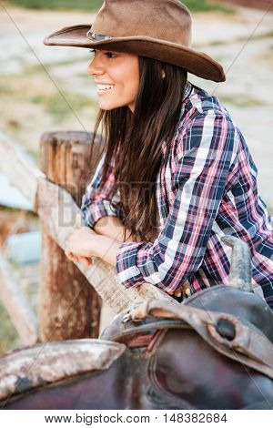 Close up portrait of a smiling happy cowgirl leaning on fence at ranch