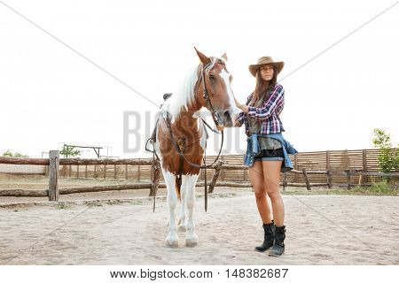Cheerful cute young woman cowgirl walking with her horse in a farm
