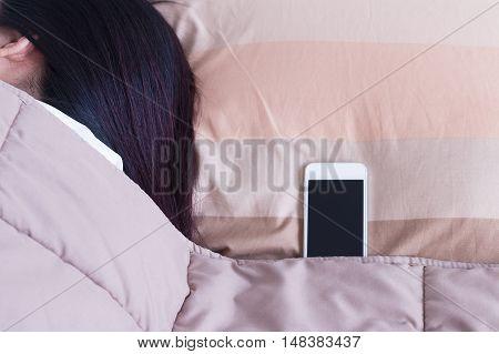 Women sleeping with mobile phone in bedroom.