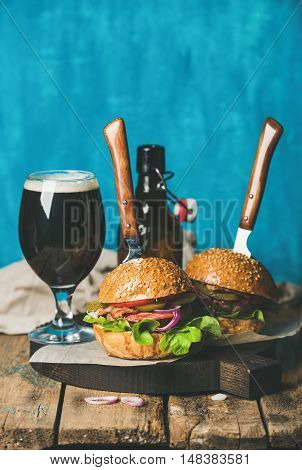 Two homemade beef burgers with crispy bacon, onion, pickles, vegetables, glass and bottle of dark beer on wooden board over rustic table, blue plywood wall at background, selective focus, copy space