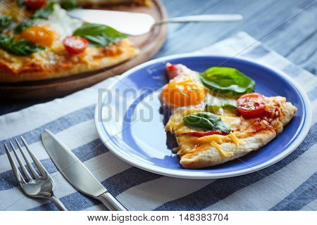 Piece of Margarita pizza with basil leaves and egg on plate closeup