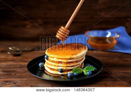 Tasty pancakes with blueberries and honey on table