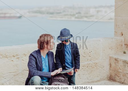family travel in Europe- father and little son looking at map in Malta