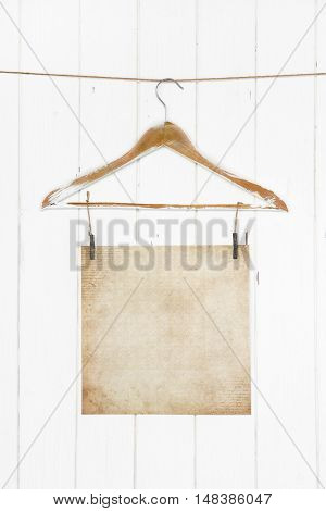 Old grunge brown paper hanging on a coat hanger on white wooden background. Mock up empty and nobody.