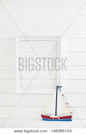 One sail boat on a white wooden background with a picture frame in mock up style empty and nobody for concepts.