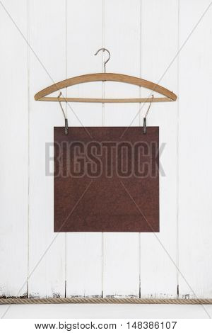 Old white brown paper hanging on a coat hanger. Mock up concept in old style empty and nobody.