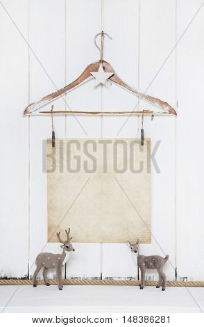 Shabby chic christmas background with an old paper and a reindeer on wooden white background.
