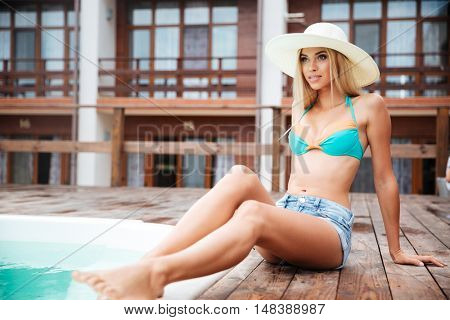 Full length of attractive young woman in hat and swimsuit sitting near swiming pool