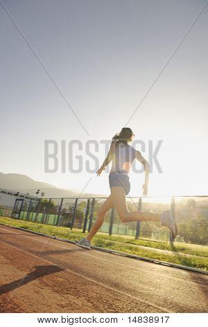Beautiful young Woman Übung Joggen und sportlich unterwegs auf Stadion bei Sonnenaufgang