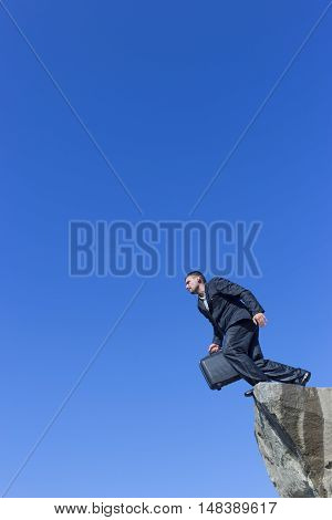 Businessman jumping with a briefcase on a background of blue sky
