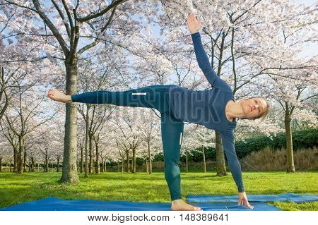 Young woman practising a half moon pose in a spring park. This pose helps to improve coordination and sense of balance
