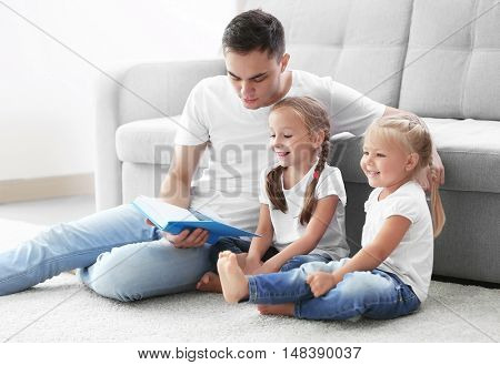 Happy father with daughters reading book
