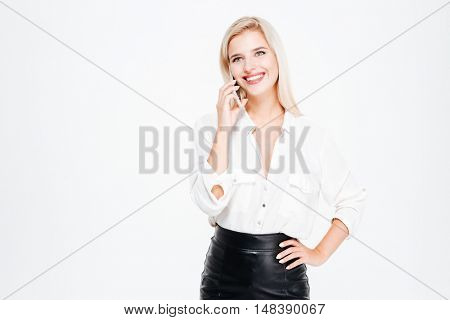 Cheerful young businesswoman standing and talking on mobile phone over white background