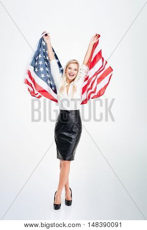 Full length of happy attractive young businesswoman holding big flag of America over white background