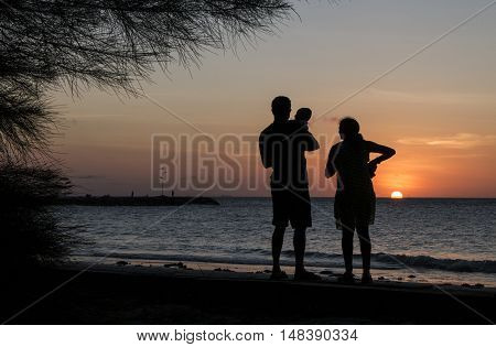 Silhouette Father and mother holding son's during sunset at the beach Kg.Pohon Batu LABUAN F.T , MALAYSIA, January 2016