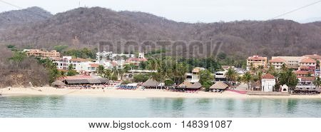 The panoramic view of Bahia de Santa Cruz town beach in early morning (Huatulco Mexico).