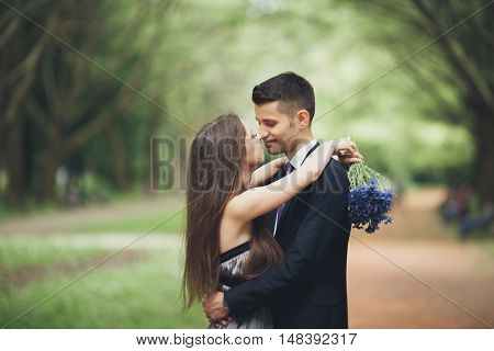 A young beautiful couple, girl with perfect dress posing in park.