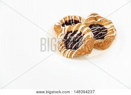 Three Danish Cherry pastries on a white porcelain plate isolated on white background. Positioned in top right corner for copy space.