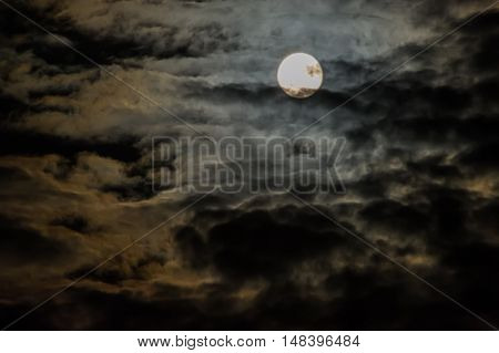 bright moon on a dark sky with clouds