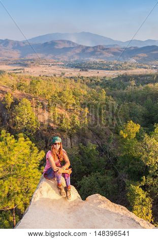 Pretty girl stay on the top of the mountain and see to the horizon with beautiful background. Colorful photo of the natural sunset over the sea.