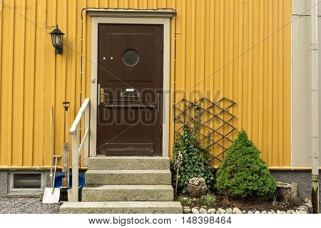 Wooden door with porch and railing arborvitae spruce garden
