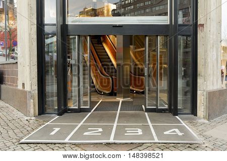 Sliding glass doors and an escalator in the Mall with number.