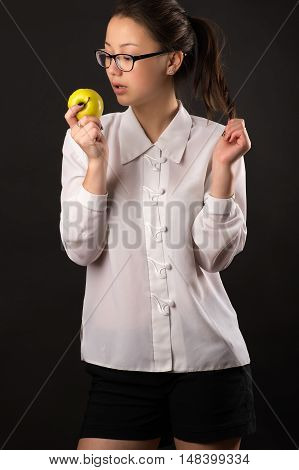 sensual teenager girl looking an apple isolated on black