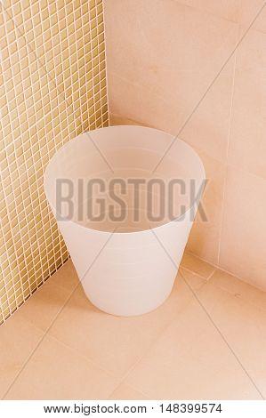 Simple plastic bin in corner of bathroom