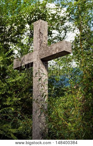 Detail of a grey marble Christian cross with green trees. Trentino Alto Adige Italy