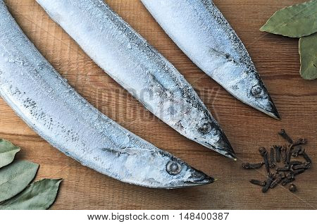 Frozen Fish Pacific Saury On A Wooden Board With Spices