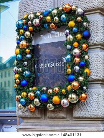 Zurich, Switzerland - 26 December, 2015: stone plate on the wall of the Credit Suisse building on Paradeplatz square with Christmas decorations. Credit Suisse Group is a Swiss multinational financial services holding company, headquartered in Zurich.