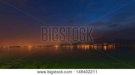 Lago di Garda at night (Garda Lake) the largest Italian lake of glacial origin with the lights of the coast of Lombardy and starry sky Italy