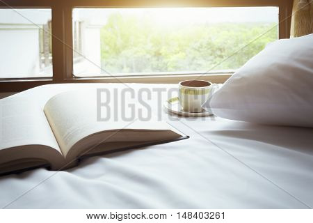 Book And A Cup Of Coffee On Bed In Bedroom.