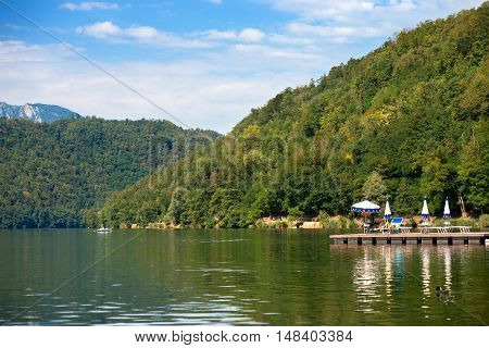 Coast of Levico Lake (Lago di Levico) with tourists swimmers and sunbathers. Levico Terme Trentino Alto Adige Italy Europe