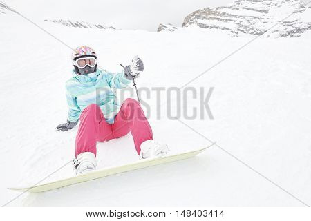 Female snowboarder wearing colorful helmet, blue jacket, grey gloves and pink pants sitting with snowboard on snow and preparing for ride - snowboarding concept