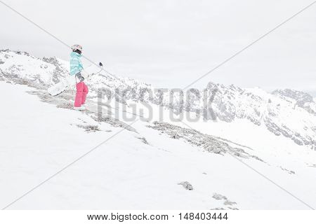 Female snowboarder wearing colorful helmet, blue jacket, grey gloves and pink pants standing with snowboard in one hand and enjoying alpine mountain landscape - snowboarding concept, copy space