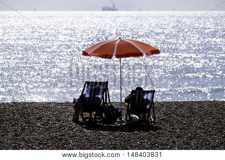 the silhouettes of two people sitting in deckchairs on pebbly beach under a red umbrella looking out to sea
