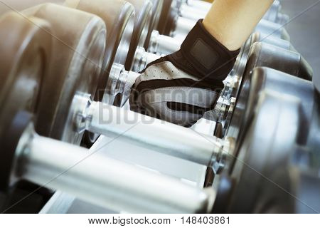 Hand Holding The Dumbells In The Gym.