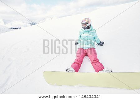Female snowboarder wearing colorful helmet, blue jacket, grey gloves and pink pants sitting with yellow snowboard on snow and preparing for ride - snowboarding concept