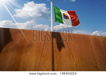 Italian flag with emblem of the four Maritime Republics Venice Genoa Pisa and Amalfi hanging on a ship's mast on blue sky with clouds and sun rays