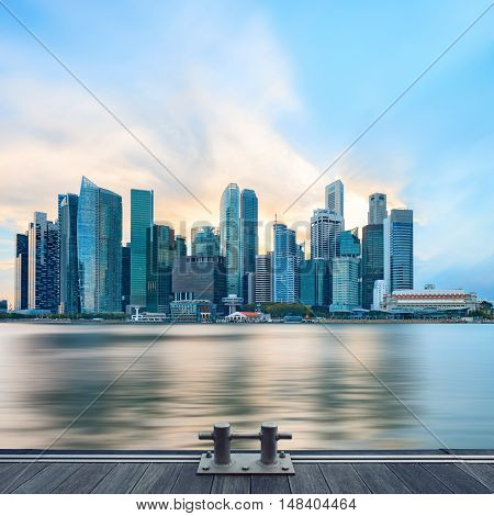 Panorama of Singapore central quay with water on foreground. Modern city architecture at sunset