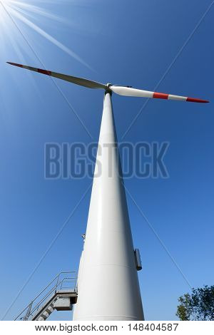 White and red wind turbine with sun rays on a clear blue sky