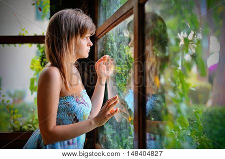 Lonely girl in green gazebo with window on the garden