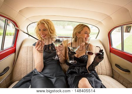 Two fancy woman sitting in retro car and enjoying life