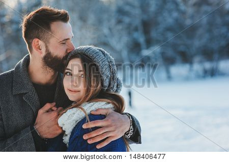 lifestyle shot of young happy couple walking in snowy forest spending winter vacation outdoors