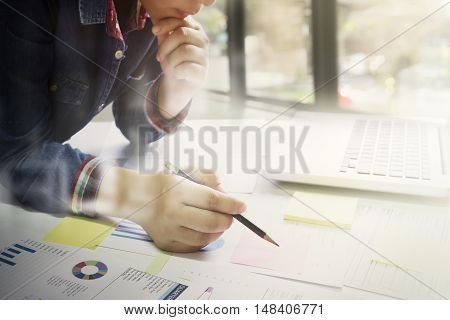 Startup business woman working with business documents on office table with graph financial diagram.