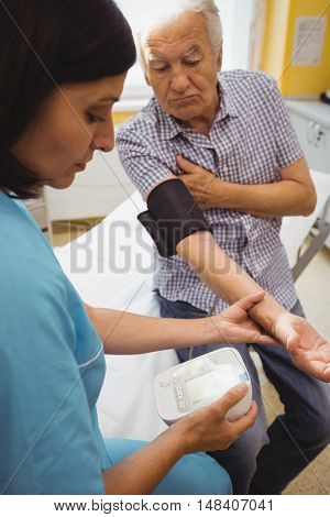 Female doctor checking blood pressure of patient at the hospital