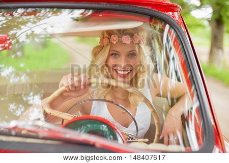 Portrait of woman driving a red vintage car